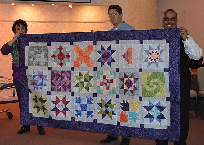 Jean Stone, Jack Trumbull and Tim Willis display the quilt donated by the Columbia River Gorge Quilters Guild for Anderson's Tribute Center Celilo Chapel location in The Dalles.