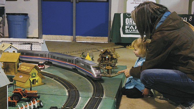 Jenavieve Camillo, 2, watches in anticipation as the model trains circle a miniature world at the Mid-Valley Ag Fest at the Polk County Fairgrounds & Event Center on Sunday. The event was attended by more than 1,500 adults on Saturday, according to event organizers.
