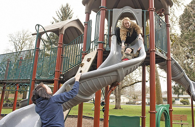 A family enjoys using a playground at Dallas City Park. Falls City, Dallas and Monmouth approved a resolution encouraging lawmakers to restore recreational immunity.