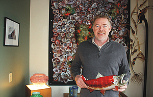 Andy Nichols, owner of Nichols Art Glass at 912 W. Sixth Street, shows off one  of his colorful blown-glass creations of his favorite subject, fish. Nichols is planning to temporarily close his shop for renovations that reflect his desire to focus on making more fish artwork.