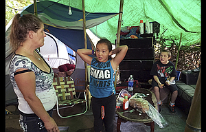 Deitra Schmer watches as her granddaughter, Andrea Brown, brushes her hair and grandson Adrian Atkinson, right, looks on in Schmer's tent in a homeless encampment along the Springwater Corridor bike and pedestrian trail in Portland.