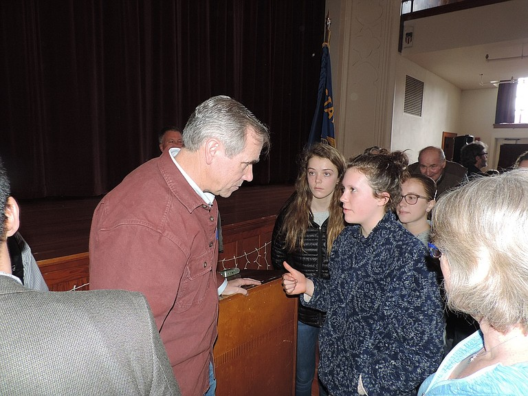 MIDDLE SCHOOL students Olivia Sumerfield, center, and Isabella Simpson speak with Sen. Merkley after the town hall. Several people at the town hall, including their friend, Josephine Stenn, had asked Merkley about President Trump's proposed military budget increase, which Merkley criticized in his remarks.