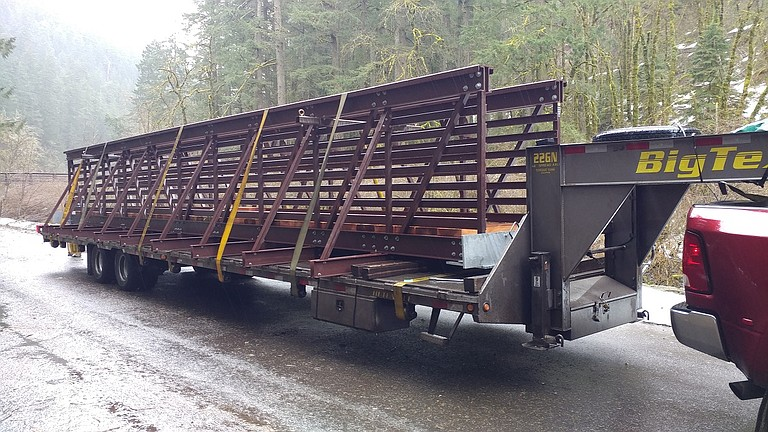 A NEW BRIDGE was delivered in late February to Tish Creek on Eagle Creek Trail. The 41-foot truss structure replaces an older bridge that was wiped out by a storm. A truck, pictured at right, towed the bridge to an area near the site, and a helicopter flew it the rest of the way.