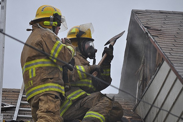 Firefighters break through a roof vent for access to a fire last Wednesday, March 8, at 511 South C Street.