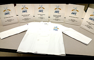 "This photo shows the chef coat that will be given to each of six student chefs who will vie for a grand prize at Saturday's ""Sodexo Future Chefs Challenge."" Pictured are the placards for each of the participating students."