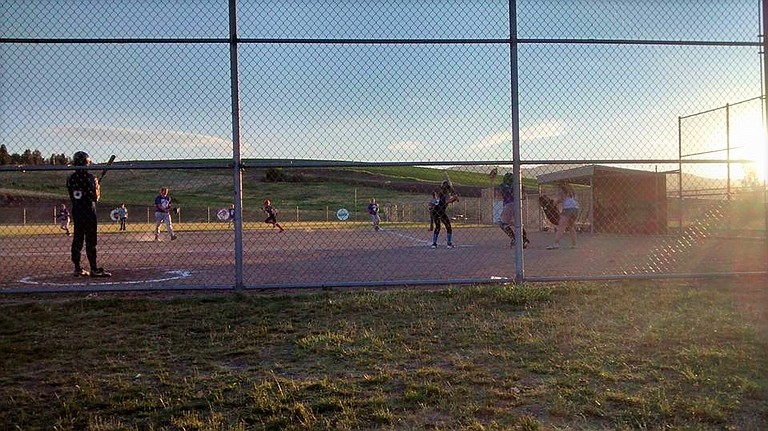 A summer softball team plays an early evening game at Wimer Field in 2015.