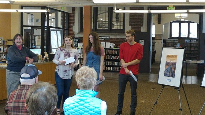 Helen James presents poster contest winners Gabby Shepard (third), Alivea Harsanyi (second) and Liam Longland (first) with their awards.