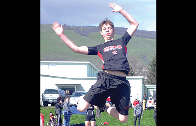 Dufur High School track and field athlete Derek Frakes leaps in the air during his jump event. At Hood River on Tuesday, Frakes placed second in the triple jump.
