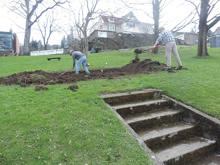 Santos Oropeza and his son, Gama, dig the space for the Minoru Yasui Legacy Stone that will be put into place as early as this week next to the library.