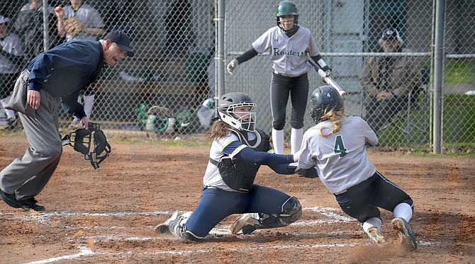 HRV SOFTBALL had commanding wins this week, especially in the team's Thursday home game with Reynolds, where the Eagles defeated the Raiders 10-1. Above left, catcher Mackenzie Chambers prevents Reynolds' Sarah Stanfill from scoring.