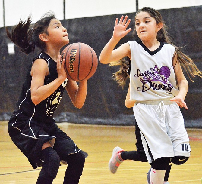 Anapaola Razo of Zillah's Z-Kids looks for the basket as Zillah Dunkin Divas' Fatima Rincon seeks to defend the shot.