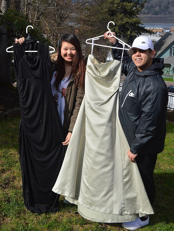 David Kirschbaum, right, and Anh Tran hold up samples of formalwear that will be available during the April 8 Dress for Less prom sale. Kirschbaum has tackled the annual sale for his EA project.