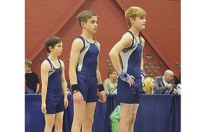 Riverside Gymnastics Academy athletes, pictured from left to right, Kayden McCavic, Steven Stanley and Nick Keilman, await their turn on the floor exercises at a recent meet in Eugene. The boys' team enjoyed success and built a solid future foundation.           Sarah Smith/Contributed photo