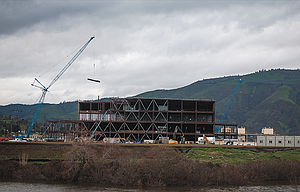 A tall crane lifts a beam to the top of a Google building under construction at the Port of The Dalles  Wednesday afternoon. The building was photographed from the Riverfront Trail, looking over Chenowith Creek. Immediately behind the photographer is the current Google server facility.