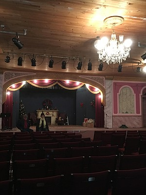 A historic Seattle chandelier graces the theatre at the Kooskia Opera House. Mike Graves, current owner, visits with Cindy Lance, cultural committee member, on the stage.