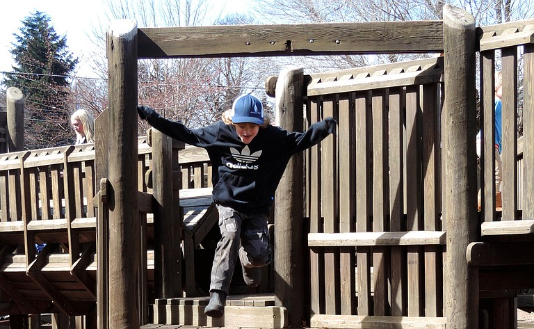HUNTER QUINNETT, 7, of Parkdale, leaps over his father, Mike, at Hood River Children's Park on Thursday, which proved to be the last full day at the playground structure for awhile. City crews closed the play structure Friday morning and put chain link fence around that section of the park.