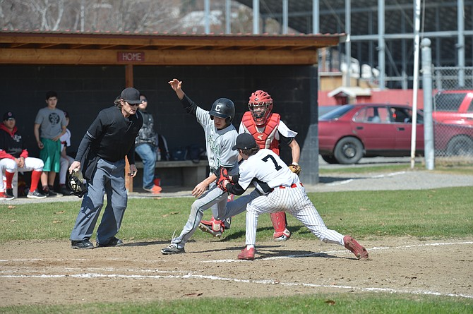 Omak pitcher Dustin Hollowell tags out a Chelan runner during game Saturday at home.