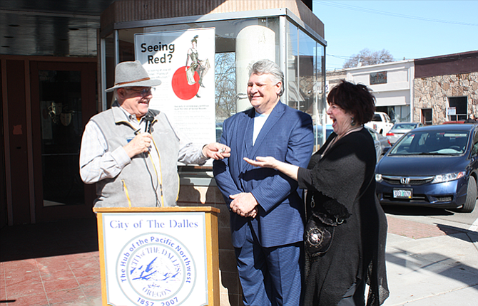 On a sunny Friday afternoon, The Dalles Mayor Steve Lawrence (left) hands over the keys for the Granada Theater to the new owners, Charles Gomez and Debra Liddell.