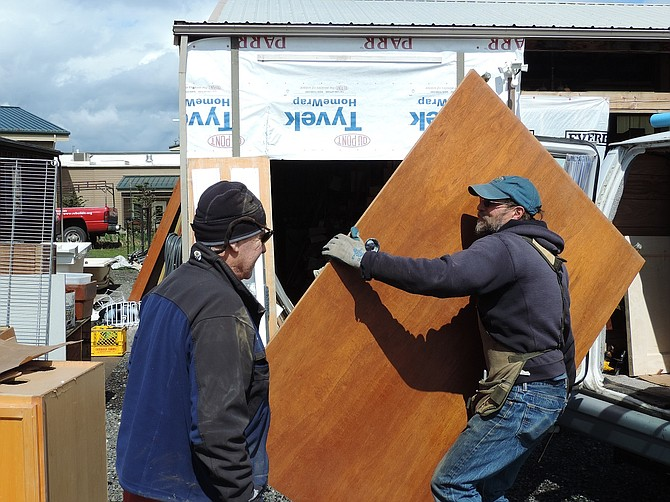 """REBUILD-IT General Manager Patrick Morris accepts donation of doors and other materials Thursday from Matt Ryan of Underwood, Wash. """"Stuff is coming in and people are shopping,"""" Morris said."""