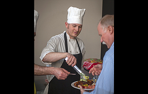 "Andrew Johnson with Cousin's Inn and Restaurant serves salad with a smile during ""An Evening With HAVEN"" Thursday night at the Fort Dalles Readiness Center. The fundraising event brought together culinary experts from throughout The Dalles."