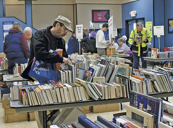Customers look through books at the Friends of the Dallas Library's book sale on Friday. The two-day library fundraiser featured hardcover and paperback booksof all genres. If you missed the  event last weekend, the friends hold a second sale in October.
