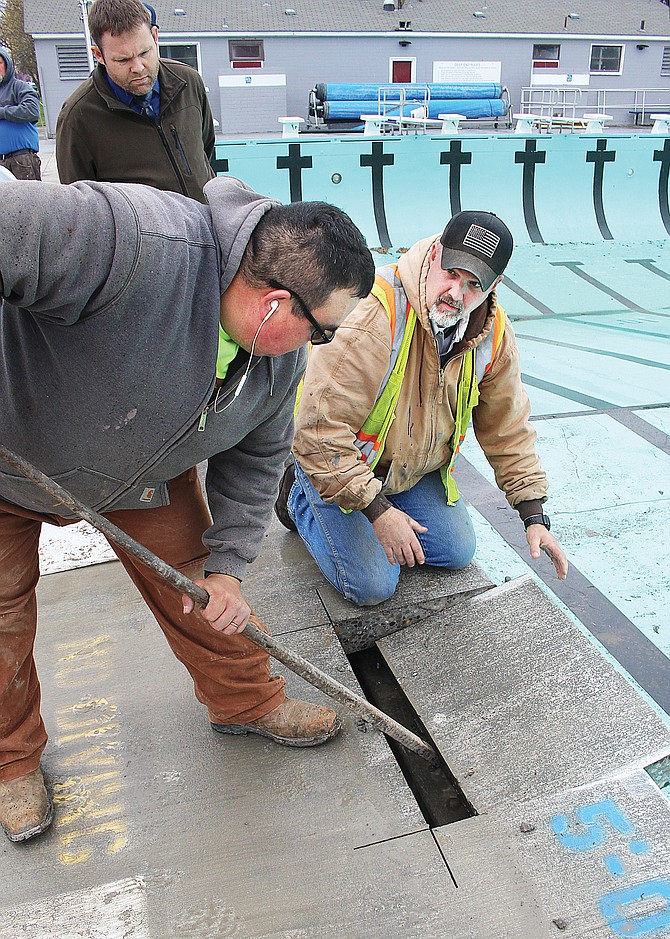Grandview Public Works and Parks and Recreation crews are busy this week with upgrades at the city pool. Yesterday, Yesterday morning, the team cut the pool deck as they prepared to install new slides at the water park on West Second Street. Pictured, Assistant Public Works Director Santos Trevino uses a crowbar to pry out a section of the pool deck as city employee Scott Smotherman prepares to remove it.