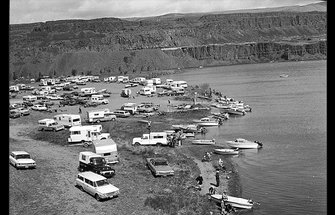 """Larry Hoctor, Gary Conley, Ken Lenke of Klickitat, Tom Davis of Redmond, Ed Goodman, and Michael Houser all contributed to this report. Last week's History Mystery photograph, above, was scanned from a 2¼- by 2¼-inch black and white negative from the archives of The Dalles Chronicle. Information on the envelope reads, """"Horsethief Lake, Opening Day, about 1970."""" Ed Goodman wrote the photograph was taken prior to the creation of Horsethief Lake State Park. """"The photo appears to be the opening day of Trout fishing season.  If I am not mistaken, that is my father Albert's 1960 Rambler station wagon at the bottom of the photo, he often parked in that spot,"""" he said."""