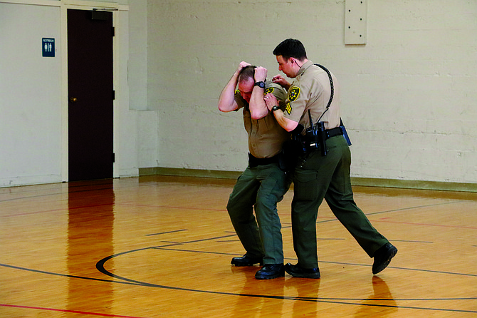 Sgt. Mike Redding and Sgt. Jason Ball demonstrate a self-defense technique during a class on Saturday morning.