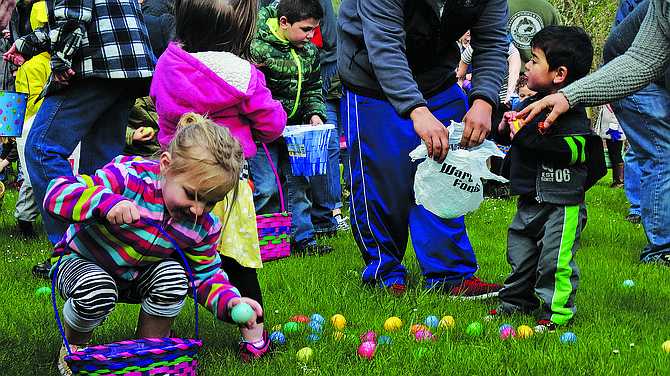 Braylin Brooks, 3, (left front) adds a plastic Easter egg to her basket on Saturday. Naethan Flores, 2, (right) takes in the scene at Gentle Woods Park, home of the annual Monmouth-Independence YMCA's Easter egg hunt. The Boy Scouts and members of Central Lions Club helped fill each egg, which contained prizes such as balloons, pencil sharpeners, or tickets that could be redeemed for free books. The Easter Bunny visited with youngsters all morning. Two golden eggs, one in each age group, represented special Easter basket giveaways. For more photos from the event: polkio.com.