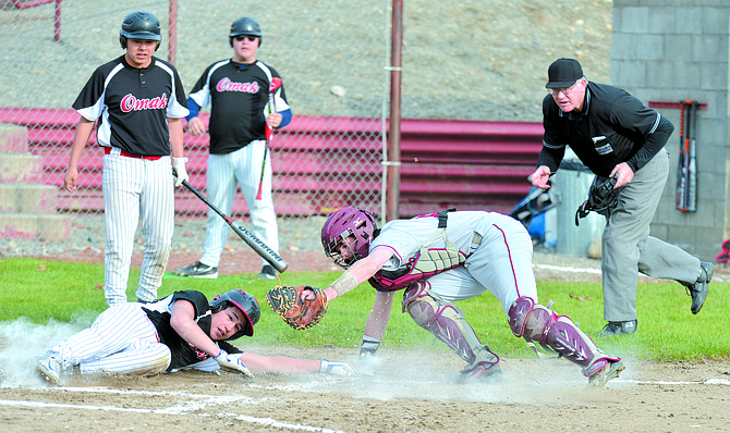 Brandon Cate of Omak scores just past Okanogan catcher Chase Rubert. The umpire is Dave Kirk.
