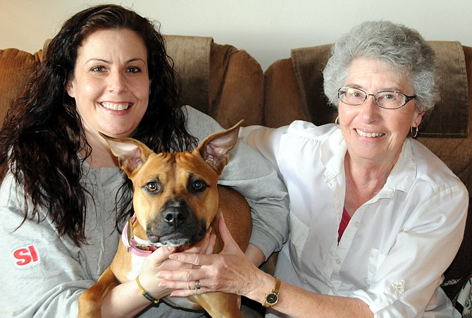 Honey the dog is right at home with her owner (left) Carolyn Kuert and her other mother (right) Nona Donaldson. The two share the dog who was formerly a stray and fostered by Kuert, an Animal Ark volunteer.
