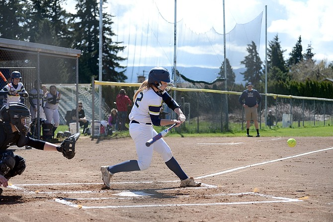 ZOE MUNN (left) takes a swing during the first game of a doubleheader with Hermiston Saturday.