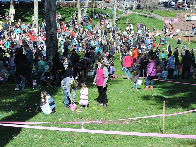 YOUNGSTERS, AND OLDER HELPERS, fill the main lawn and parking lot at Jackson Park for the community egg hunt and Children' Safety Fair, both held under prime sunny skies.