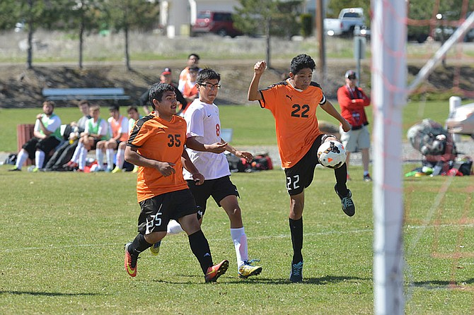 Miguel Rojas of Omak, No. 8, defends against Edward Martinez, No. 35, and Daniel Valdovinos, No. 22, in a match April 15 in Omak.