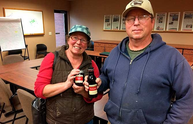 Mary Leighton and her brother, Chuck Sandoz, pose for a photograph with some of the farms' product, cherry jam and cherry juice. Both are prepared and bottled in a commercial kitchen at the farm on Mill Creek Road.