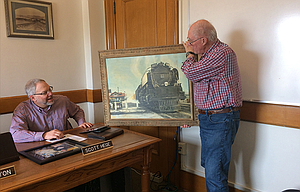 Anders Andersson, right, presents an original artwork of late artist Wilma Roberts to Commissioner Scott Hege at an April 5 public meeting. After displaying the image at the Wasco County Pioneers Association in May, county officials will decide where it should be displayed.