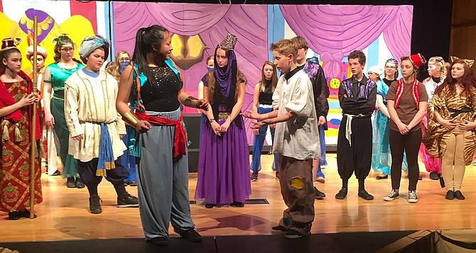 Aladdin, played by Jack Wilson, grants Genie, played by Bridget Bomglamphone, her freedom. Jasmine, played by Sierra Lavoie, looks on with the rest of the cast.