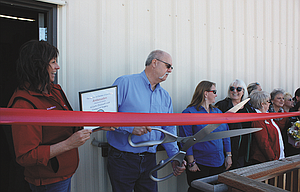 Joe Perry, CEO of Wilson Orchard & Vineyard Supply, wields the big scissors as the business celebrates the opening of a new store in The Dalles on Friday with members of The Dalles Area Chamber of Commerce. The business is located at 210 Webber Street.
