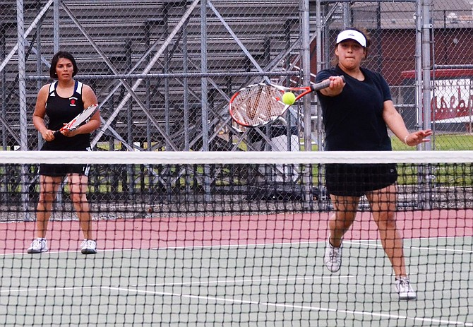 Sunnyside No. 1 girls doubles player Stephanie Herrera returns the ball to her Davis opponents as partner Mirella Ramirez stands at the ready.