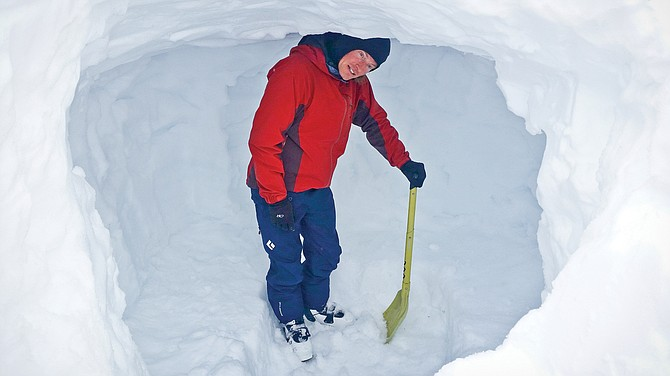 A state transportation worker digs out a snow cave on Chinook Pass. The caves are for workers' safety during snow removal efforts at the pass.