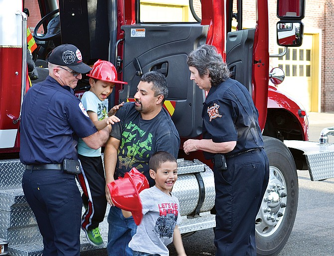Yakima Valley Fire District No. 5 responders Avilio Perez of Grandview and Diana Fahsholtz of Zillah help community members out of a fire truck after a ride last night. The rides were part of an open house the Grandview Fire Department and the distirct's Station No. 14 hosted. The event attracted about 200 people and several water fights with buckets provided by the station.
