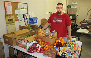 Matt Post, a board member and volunteer with Windy River Gleaners, prepares food for distribution at the Gleaners' facility at 3400 Crates Way in The Dalles.