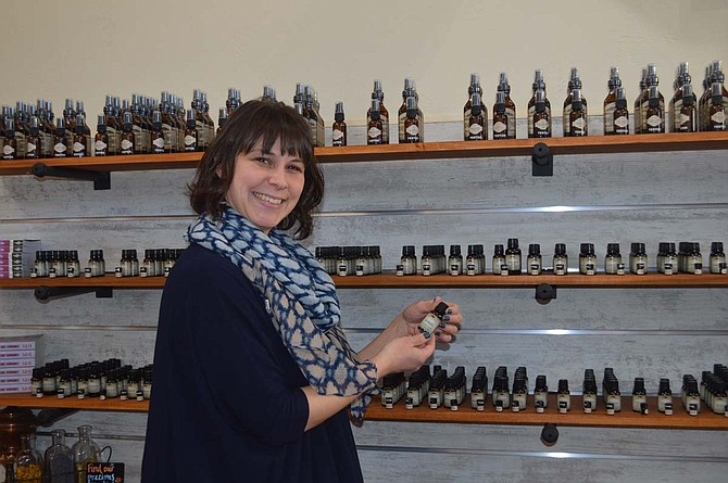 Christine Rice, product manager and staff aromatherapist, stands in front of the essential oil display at Mountain Rose Herbs Mercantile, the company's new storefront in downtown Eugene.
