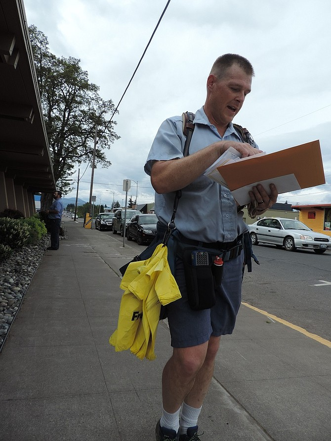 U.S. Postal Service Carrier Brad Heilman walks his beat on the Heights Thursday, and he was delivering more than mail: on his belt are yellow bags that carriers are leaving for patrons to fill with non-perishable food donations.