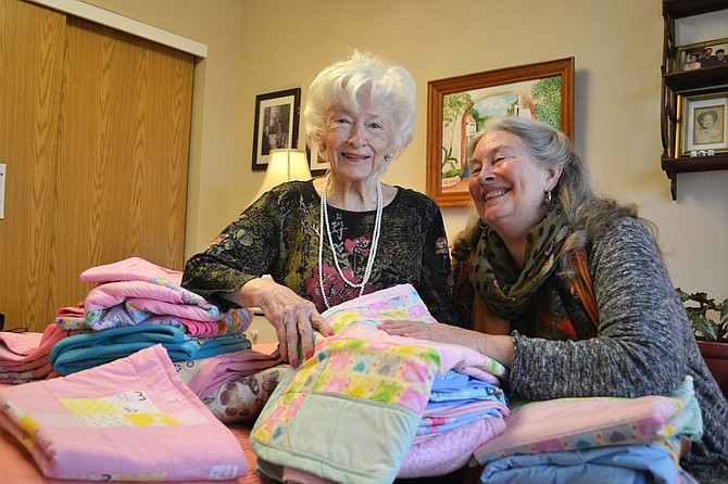 Dorothy Wallace Foisy (left) shares a tender moment with her youngest daughter Lynn Walker at Conifer Place, where Foisy now lives. She recently moved to Oregon from Florida, and has continued to sew dozens of baby blankets for families in need.