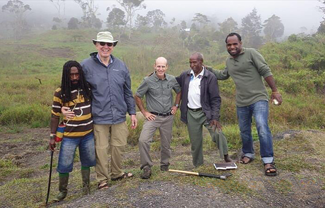 Wayne von Borstel is pictured with locals he met with in the highlands of Papua, Indonesia, seen in the background map. He was among 14 members of Calvary Baptist Church in The Dalles who visiting there to provide support for teachers, who face multiple cultural obstacles. The man next to him is holding a machete, a common tool needed in the jungle environment.