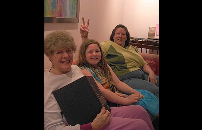 "Mary Ellen Kavanagh, left, sits on her hot pink sofa with granddaughter Gracie McLoughlin  and daughter Neita Cecil beneath one of her colorful paintings in this 2007 photo. Cecil credits her mother with being a positive role model who has taught the family to ""see the gold in people."""
