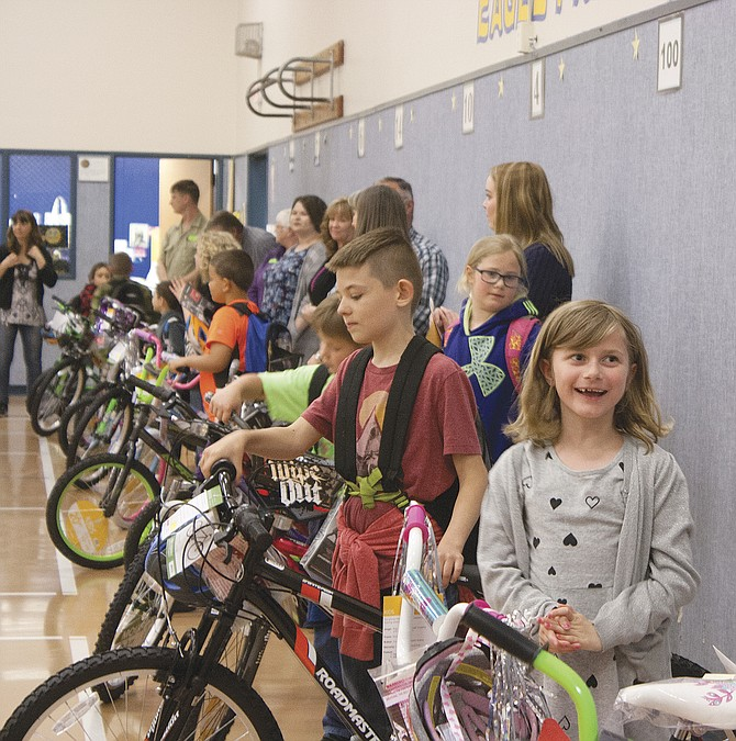 Students receive their bikes at Oakdale Heights Elementary School on Monday afternoon.