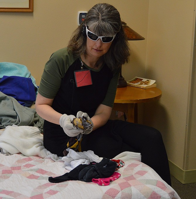 News staff writer Trisha Walker attempts to match and fold six pairs of socks during a Virtual Dementia Tour Monday at Providence Brookside Manor — a simple task made difficult with the addition of shaded glasses, headphones pumping in a constant stream of noise, and two pairs of gloves, all to simulate what it would be like to live with worse-case scenario dementia.