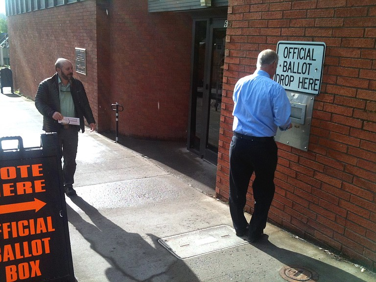 VOTERS drop off their ballots on Tuesday morning at the County Building, Sixth and State, before work.